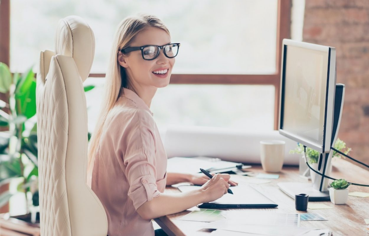 A secretary sits on a management chair with a headrest at her workstation in an office in front of the screen and is efficiently busy.